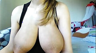 Gorgeous brunette with huge breasts plays with her pussy